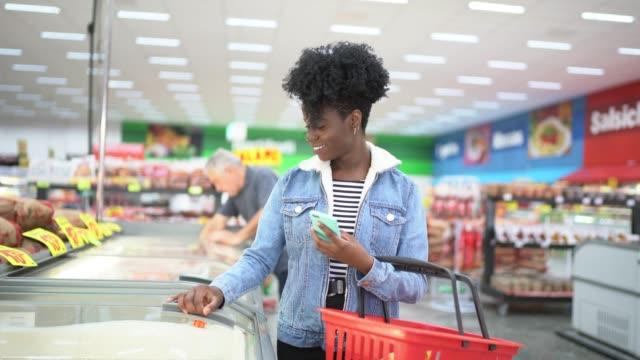junge frau auf der suche nach produkten in der supermarkt-gefrierschrank - korb stock-videos und b-roll-filmmaterial