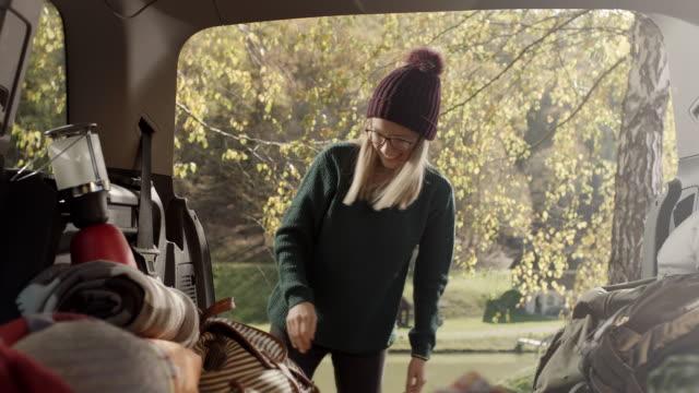 Junge Frau auf der Suche nach einige Dinge auf der Rückseite des Autos