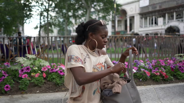 a young woman looking in her bag for her mobile phone - purse stock videos & royalty-free footage
