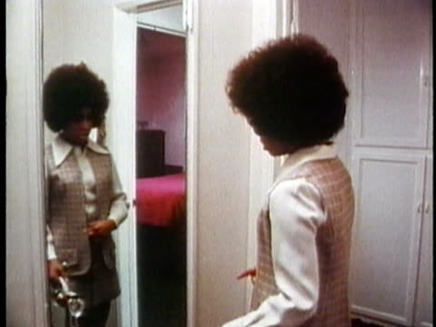 vidéos et rushes de 1971 ms young woman looking in mirror, getting ready to leave for job interview / usa / audio - coiffure afro