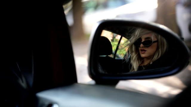young woman looking in the car mirror - rear view mirror stock videos and b-roll footage