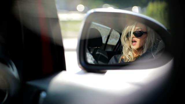 junge frau auf der suche in spiegel auto - auto innenansicht stock-videos und b-roll-filmmaterial