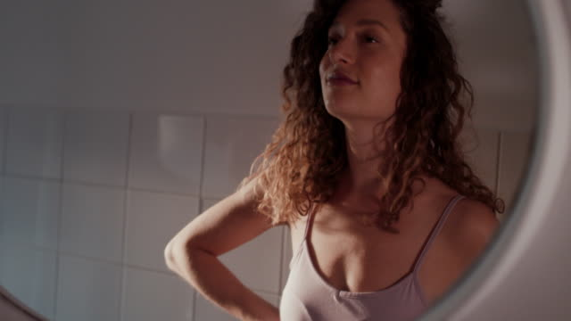 stockvideo's en b-roll-footage met young woman looking in the mirror in bathroom in morning in berlin - domestic bathroom