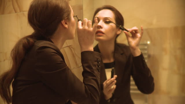 vidéos et rushes de ms young woman looking into bathroom mirror and applying make-up, new york city, new york, usa - mascara