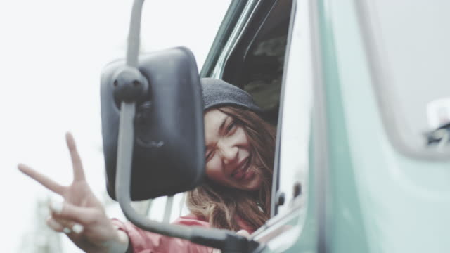 Young woman looking into car mirror and making funny faces. Sitting in a van