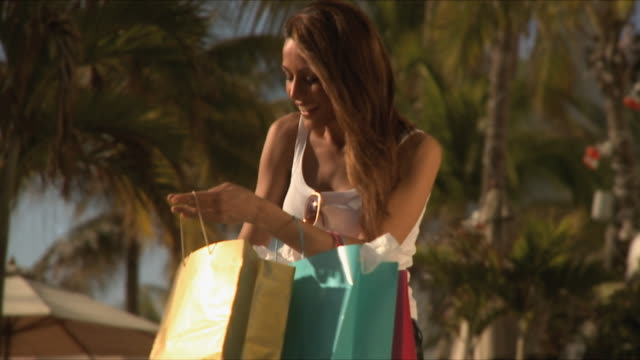 slo mo ms young woman looking into shopping bags and laughing / south beach, florida, usa - mid length hair stock videos & royalty-free footage
