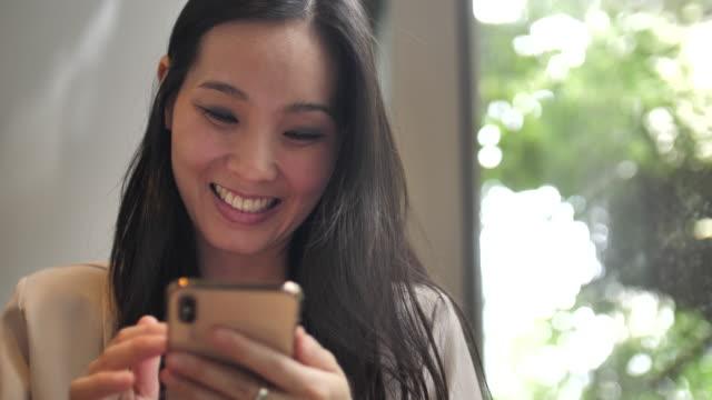 vidéos et rushes de jeune femme à la recherche sur téléphone portable - photophone