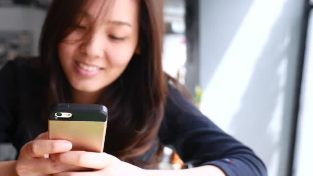 Ung kvinna tittar på Smart telefon, använder telefonen
