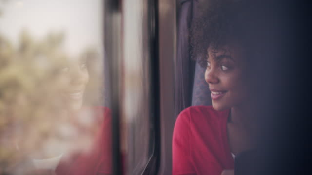 vidéos et rushes de cu young woman looking out a window on a train - coiffure afro
