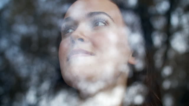 sm cu young woman looking out a window - brown hair stock-videos und b-roll-filmmaterial