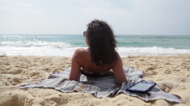 young woman looking out at beach in the south of france. - sunbathing stock videos and b-roll footage