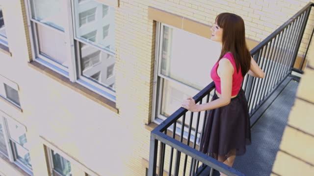 vídeos de stock, filmes e b-roll de young woman looking out from fire escape - batom rosa