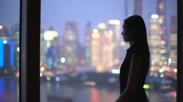 vidéos et rushes de ms young woman looking out of a window, shanghai, china - regarder par la fenêtre