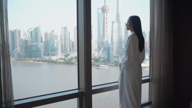 stockvideo's en b-roll-footage met ws young woman looking out of a window, shanghai - badjas