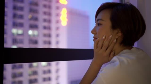 窓の外を見ている若い女性 - 窓越し点の映像素材/bロール