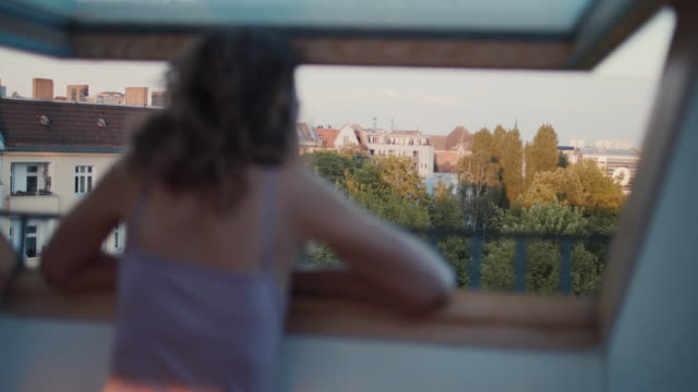 young woman looking out of loft window at berlin rooftops - vest stock videos & royalty-free footage