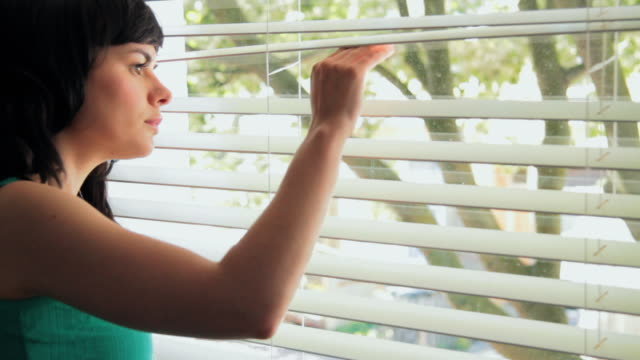 cu young woman looking out of window / london, united kingdom - blinds stock videos & royalty-free footage