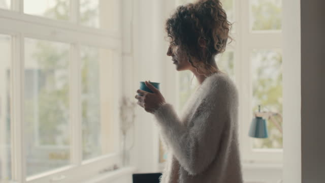 young woman looking out of window, smelling coffee at home in berlin - riposarsi video stock e b–roll