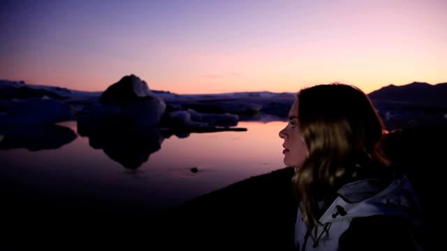 ms young woman looking out on glacial lagoon at twilight, hofn, iceland - polarklimat bildbanksvideor och videomaterial från bakom kulisserna