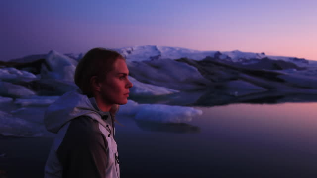 MS Young woman looking out on glacial lagoon at twilight, Hofn, Iceland