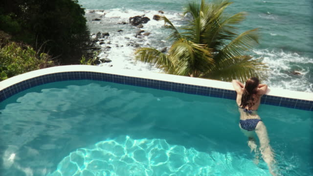 ha ws rv young woman looking out over ocean from edge of infinity pool/ scarborough, tobago, trinidad and tobago - pool mit gegenströmung stock-videos und b-roll-filmmaterial