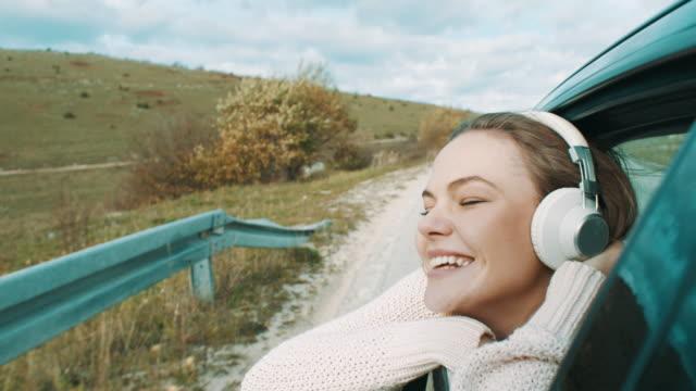 junge frau schaut aus dem autofenster und musik über kopfhörer hören - serene people stock-videos und b-roll-filmmaterial
