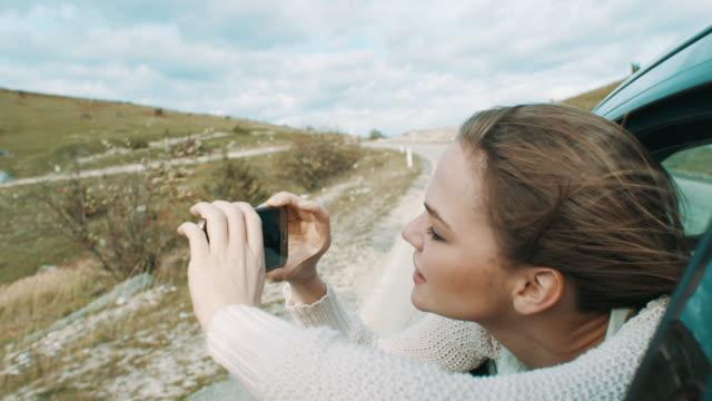 vídeos de stock, filmes e b-roll de jovem mulher olhando pela janela de carro e tirar fotos com o telefone dela - máscara