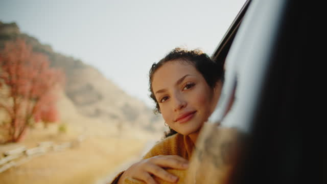 young woman looking out the car window on a road trip in the mountains - 18 19 years stock videos & royalty-free footage