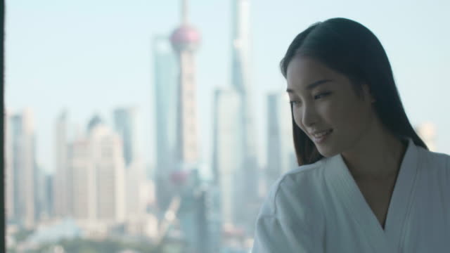 stockvideo's en b-roll-footage met cu young woman looking out window, shanghai, china - badjas
