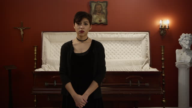 A young woman looking somber in a funeral home