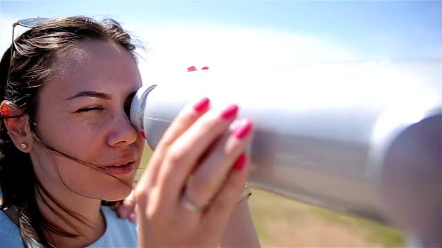 stockvideo's en b-roll-footage met jonge vrouw kijken door een telescoop - verrekijker