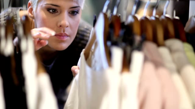 stockvideo's en b-roll-footage met young woman looking through clothes. - koopwaar
