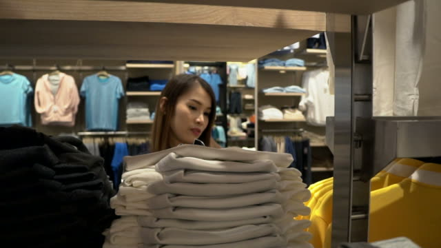 young woman looking through clothes - garment stock videos & royalty-free footage