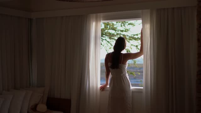 young woman looking through hotel window - memories stock videos & royalty-free footage