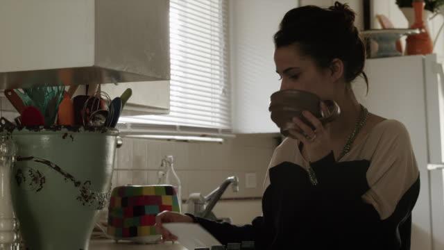 ms young woman looking through mail and making toast in kitchen / provo, utah, usa - provo bildbanksvideor och videomaterial från bakom kulisserna