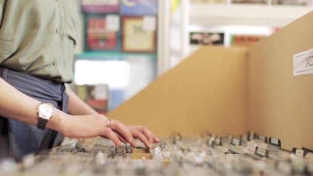 young woman looking through stacks of vinyl - music poster stock videos & royalty-free footage