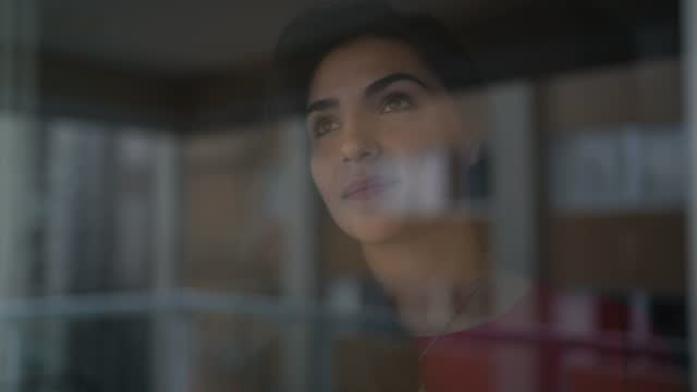 young woman looking through window - candid stock videos & royalty-free footage