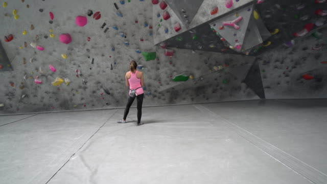 ws ds sm young woman looking up at a climbing wall - climbing wall stock videos & royalty-free footage