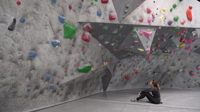 ws young woman looking up at climbing wall - climbing wall stock videos & royalty-free footage