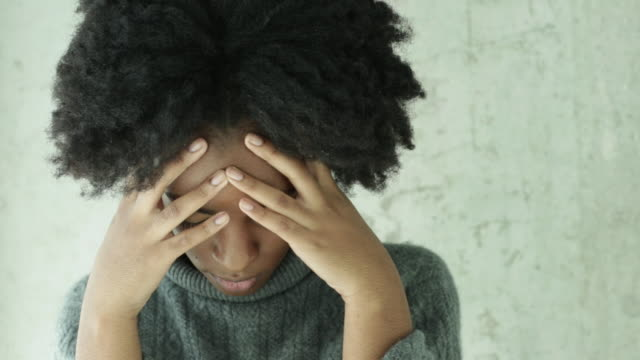 vidéos et rushes de cu young woman looking upset puts head in her hands. - d'origine africaine