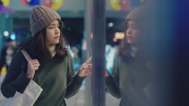 vídeos y material grabado en eventos de stock de mujer joven mirando escaparates de compras en la ciudad por la noche. - escaparate de tienda