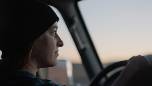 Young woman looks ahead as she drives through Utah desert at dusk.