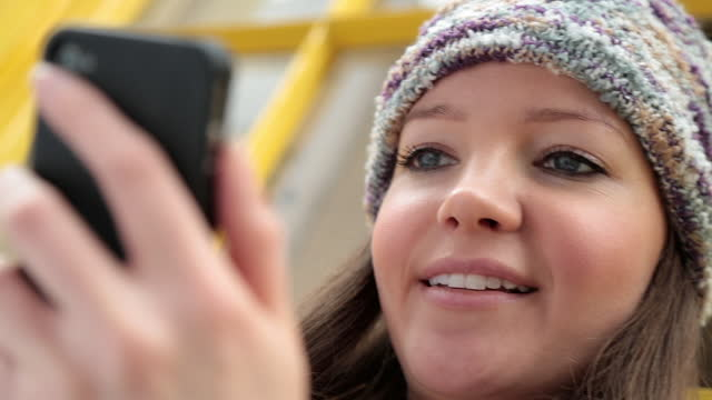 cu. young woman looks and laughs at smartphone. - non us location stock videos & royalty-free footage