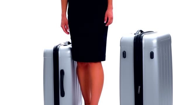 Young woman looks around, takes the two suitcases and leaves