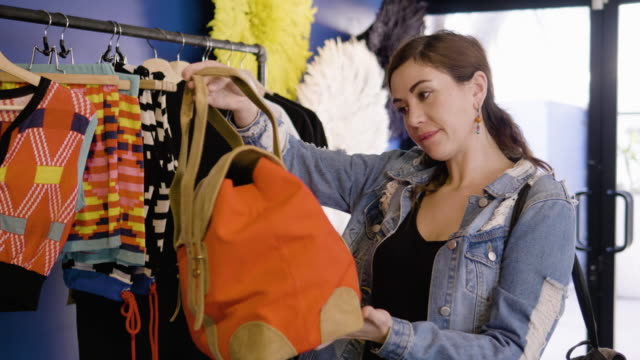 vídeos de stock, filmes e b-roll de a young woman looks at a bag in an african-themed clothing boutique - jaqueta jeans