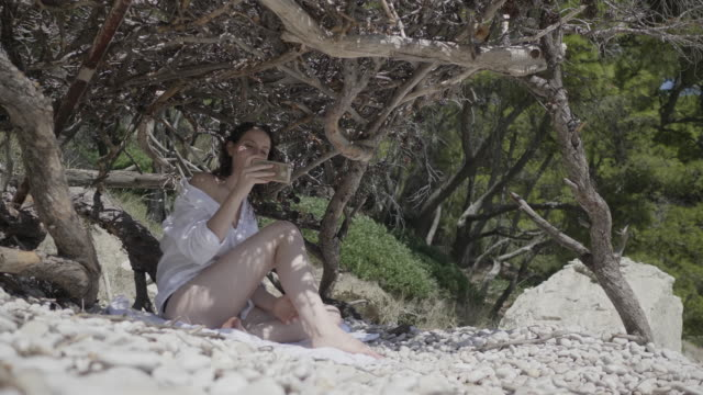 vídeos y material grabado en eventos de stock de young woman looks at cellphone on hvar beach, low angle - cultura croata