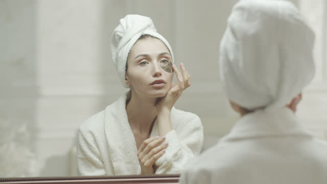 young woman looks at herself in the mirror, in a dressing gown and a towel and applies medical eye patch under her eyes with her hands. - medical dressing stock videos & royalty-free footage