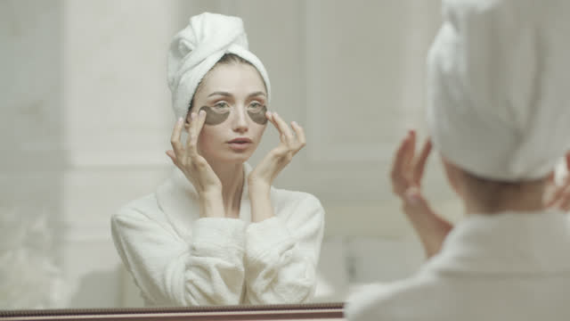 young woman looks at herself in the mirror, in a dressing gown and a towel, and with her hands adjusts the medical eye patch her eyes. - medical dressing stock videos & royalty-free footage
