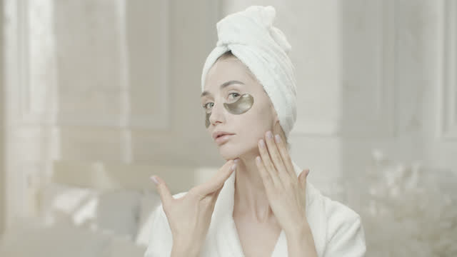 young woman looks at herself in the mirror, in a dressing gown and a towel with medical eye patch under her eyes, smears cream on her neck. - medical dressing stock videos & royalty-free footage