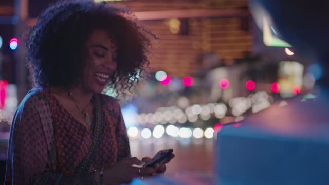young woman looks at smartphone and laughs as she texts outside las vegas casino at night. - carefree stock videos and b-roll footage